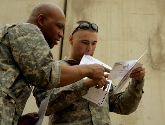 U.S. Army Cpl. Sean Morton, 25, from Boston,  right, assigned to Killer Troop, 3rd Squadron, 3rd Armored Cavalry Regiment, consults with a colleague before mailing his absentee ballot for the presidential election at Forward Operating Base Marez in Mosul, Iraq, Oct. 22, 2008.