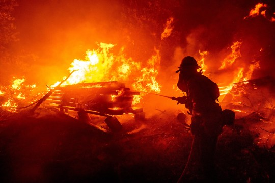 A firefighter battles the Creek Fire as it threatens homes in the Cascadel Woods neighborhood of Madera County, Calif., on Monday, Sept. 7, 2020. (AP Photo/Noah Berger) ORG XMIT: CANB103