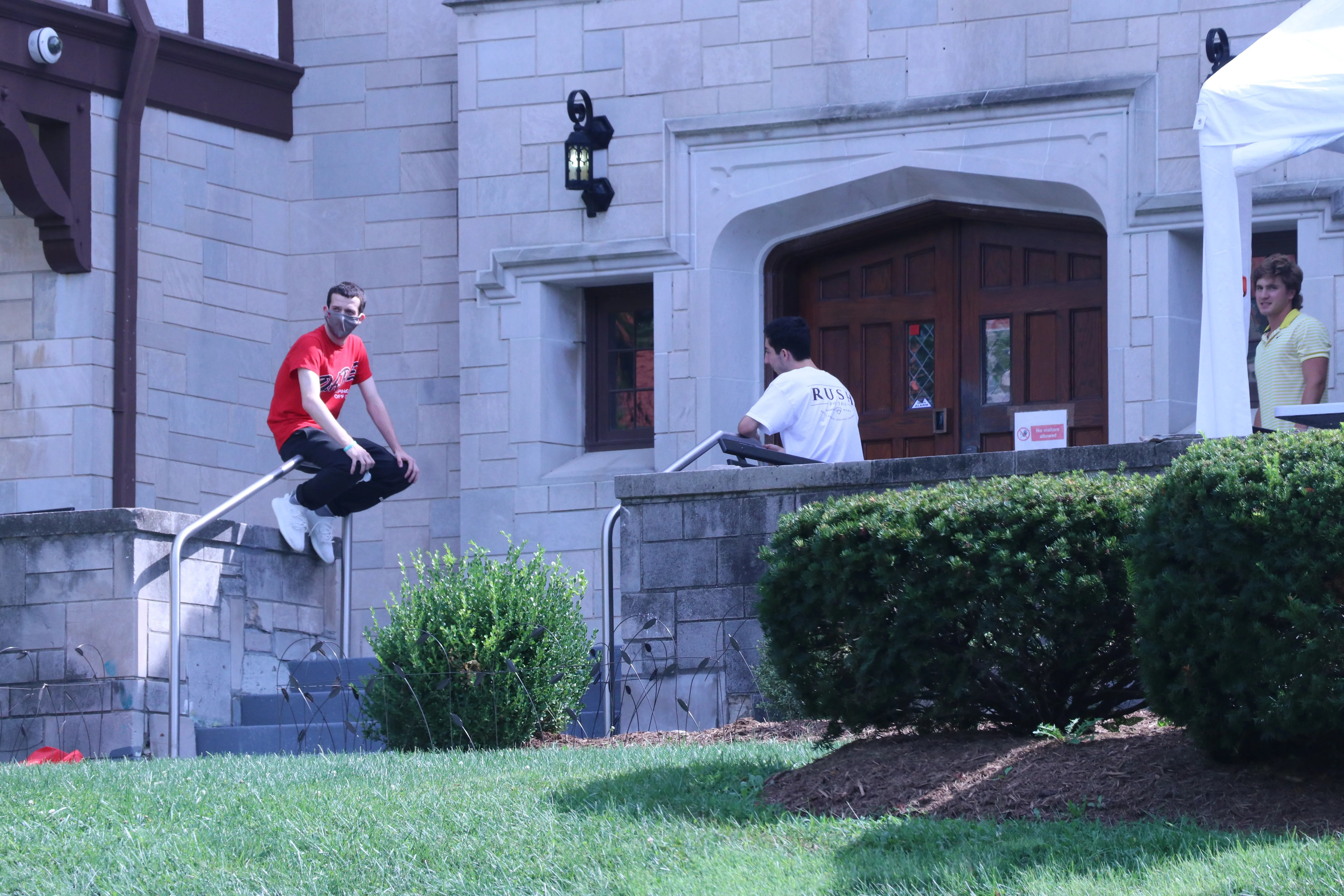 People sit outside the Phi Kappa Tau fraternity house on the Indiana University campus.