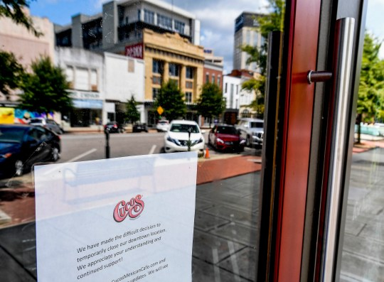 A sign in the window of the temporarily closed Cuco's restaurant in downtown Montgomery, Ala., is seen on Tuesday September 8, 2020.