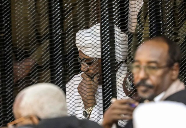 In this Aug. 24, 2019 file photo, Sudan's autocratic former President Omar al-Bashir sits in a cage during his trial on corruption and money laundering charges, in Khartoum, Sudan. A top Sudanese official said Monday, Feb. 11, 2020, that transitional authorities and rebel groups have agreed to hand over al-Bashir to the International Criminal Court for war crimes, including mass killings in Darfur. Since his ouster in April, al-Bashir has been in jail in Sudan's capital, Khartoum, over charges corruption and killing protesters.