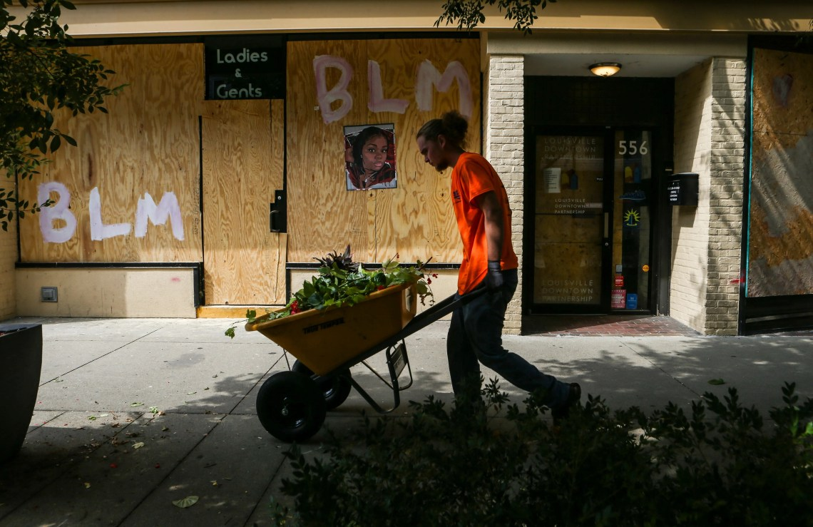 Trevor Mullins of C. Denny Landscaping takes away plants and flowers for the season while working along Fourth Street in downtown Louisville. Most businesses are boarded up and closed but a few are still open.