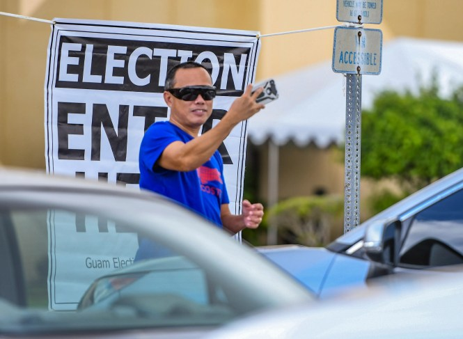 A man takes a selfie in front of an election sign during village absentee voting at Okkodo High School in Dededo Oct. 17, 2020.