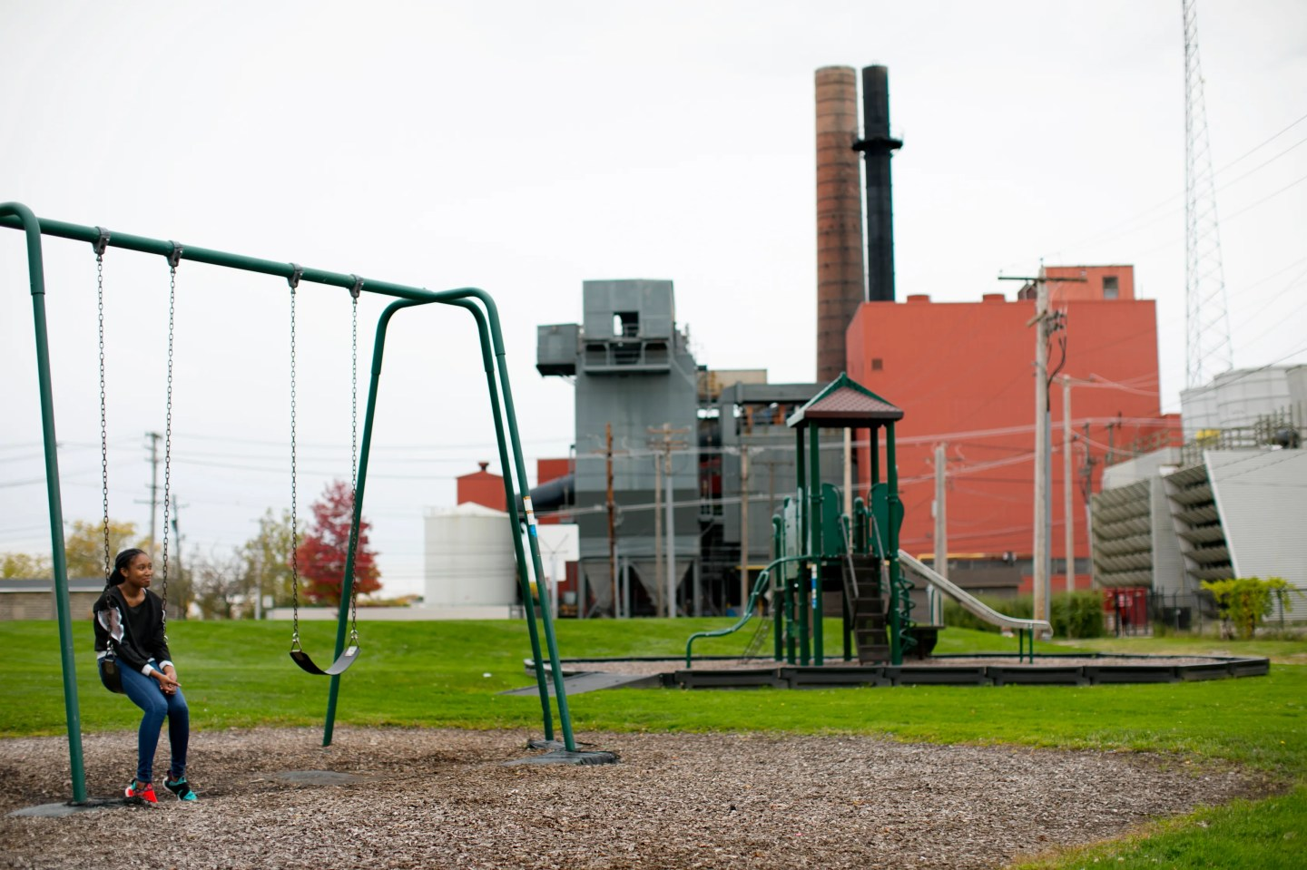 Armani Wells, 13, sits on a swing after school, just across from the city-owned power plant in Painesville, Ohio.
