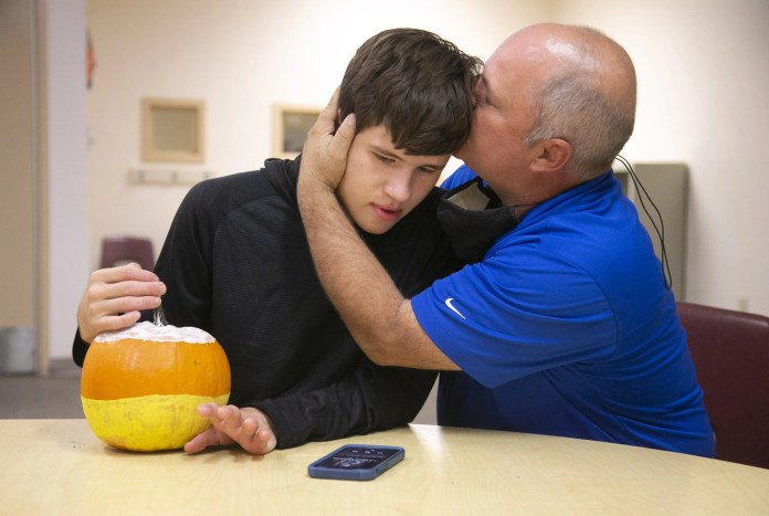 Scott Alford of Peoria, kisses his son, Sammy Alford, 20, who has autism and is non-verbal, at the Arizona Centers for Comprehensive Education and Life Skills in Phoenix on November 12, 2020. Sammy is a student at the private, non-profit school provides education and life skills for children and young adults with disabilities.