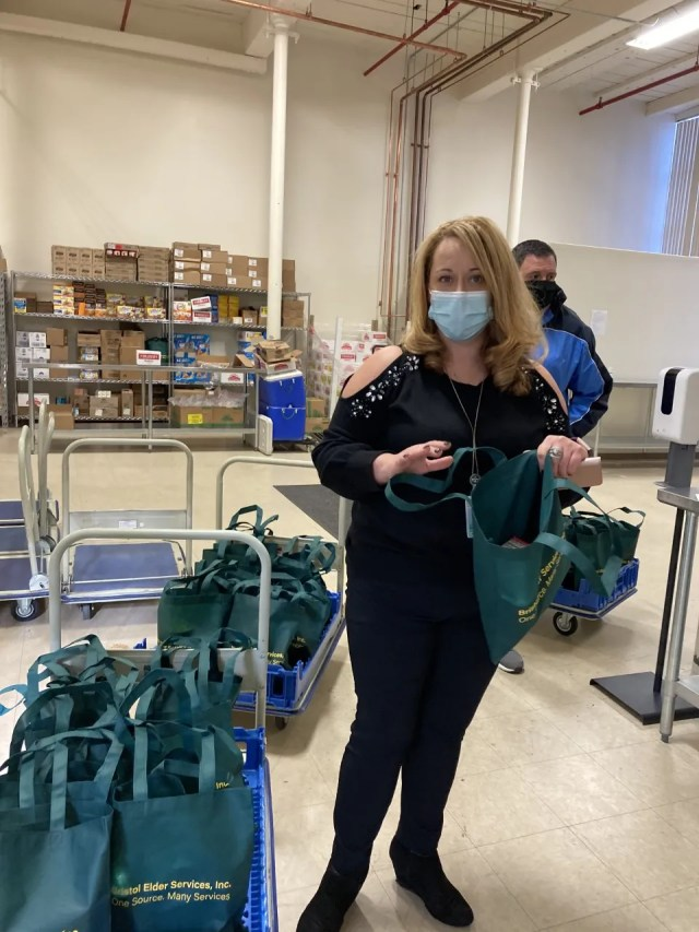 Debbie Avila-Carreiro, nutrition director for Bristol County Elder Services packs groceries for seniors in the agency's food security program.