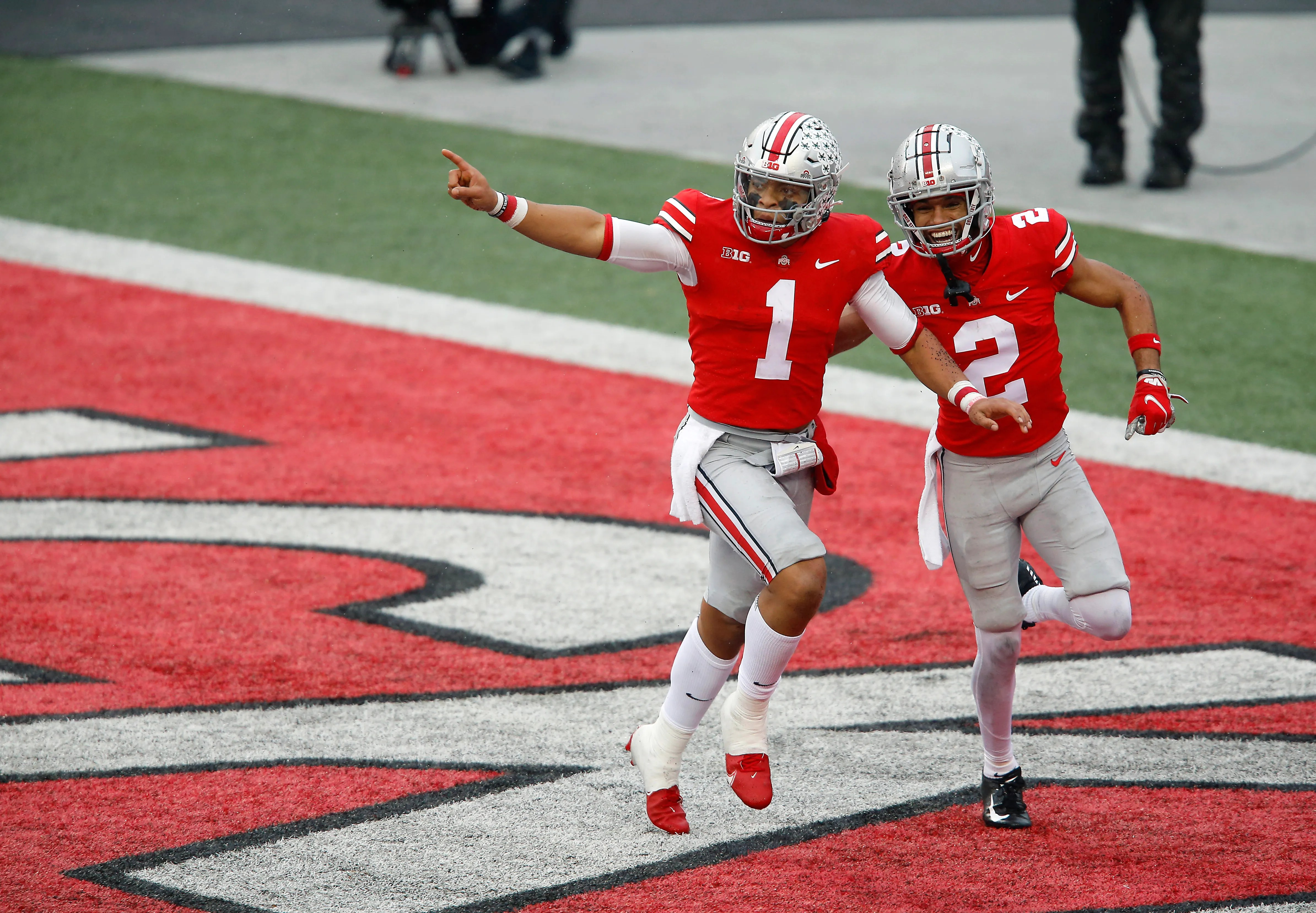 Justin Fields (1) celebrates his first-half touchdown run with Chris Olave (2).