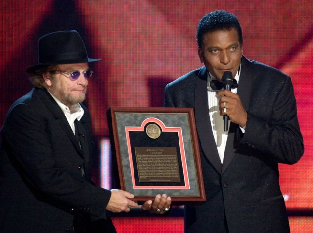 FILE - In this Oct. 4, 2000, file photo, Charley Pride, right, receives his Country Music Hall of Fame plaque from Merle Haggard at the Country Music Association Awards show at the Grand Ole Opry House in Nashville, Tenn.