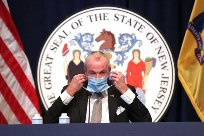 New Jersey Governor Phil Murphy puts his mask on at the end of his Monday, December 14, 2020, briefing on the State's COVID-19 response at the Trenton War Memorial