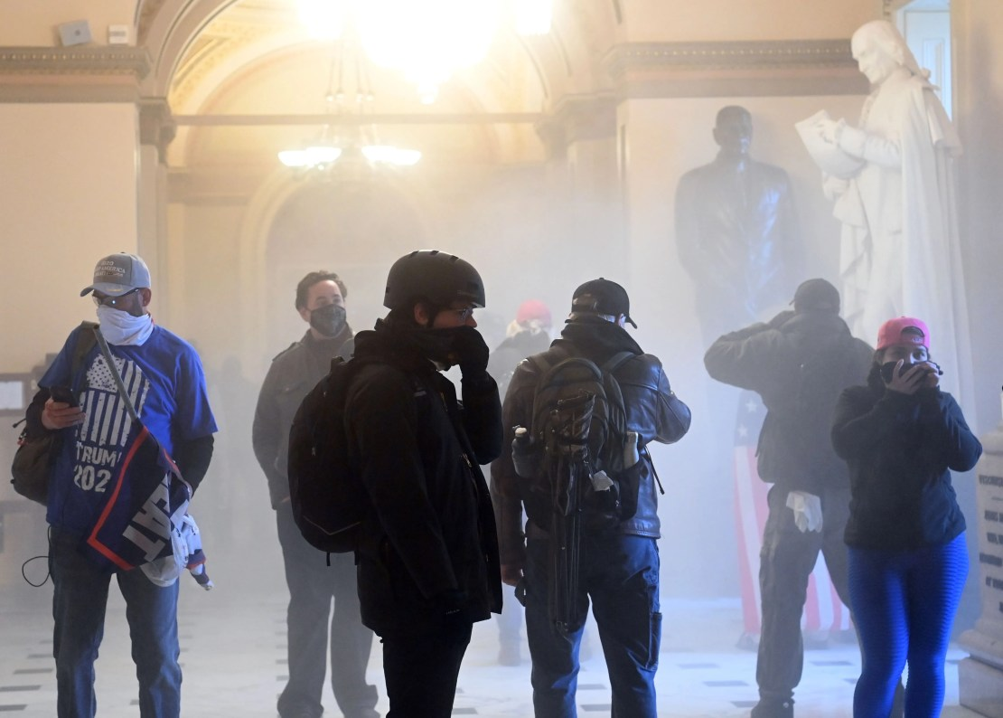 Supporters of US President Donald Trump enter the US Capitol as tear gas fills the corridor.