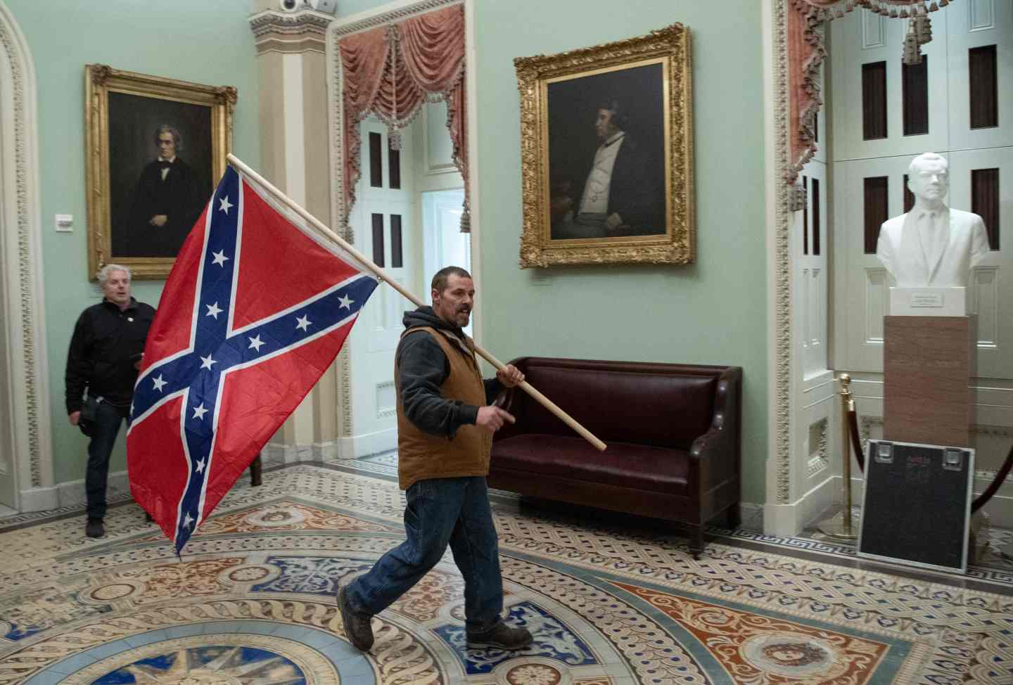 A Pro-Trump rioter carries a Confederate flag near the Capitol Rotunda on Jan. 6.