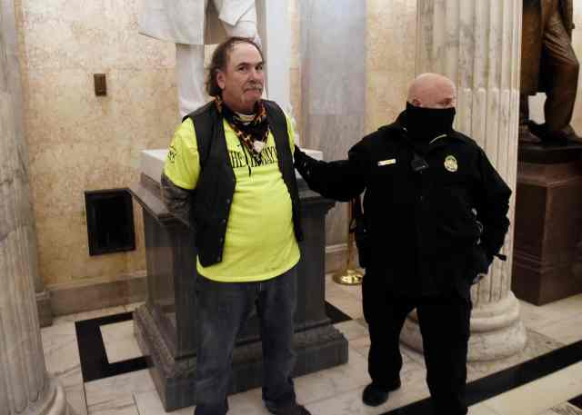 A supporter of President Trump is arrested inside the US Capitol in Washington DC on January 6, 2021.  (Photo by Olivier DOULIERY / AFP)