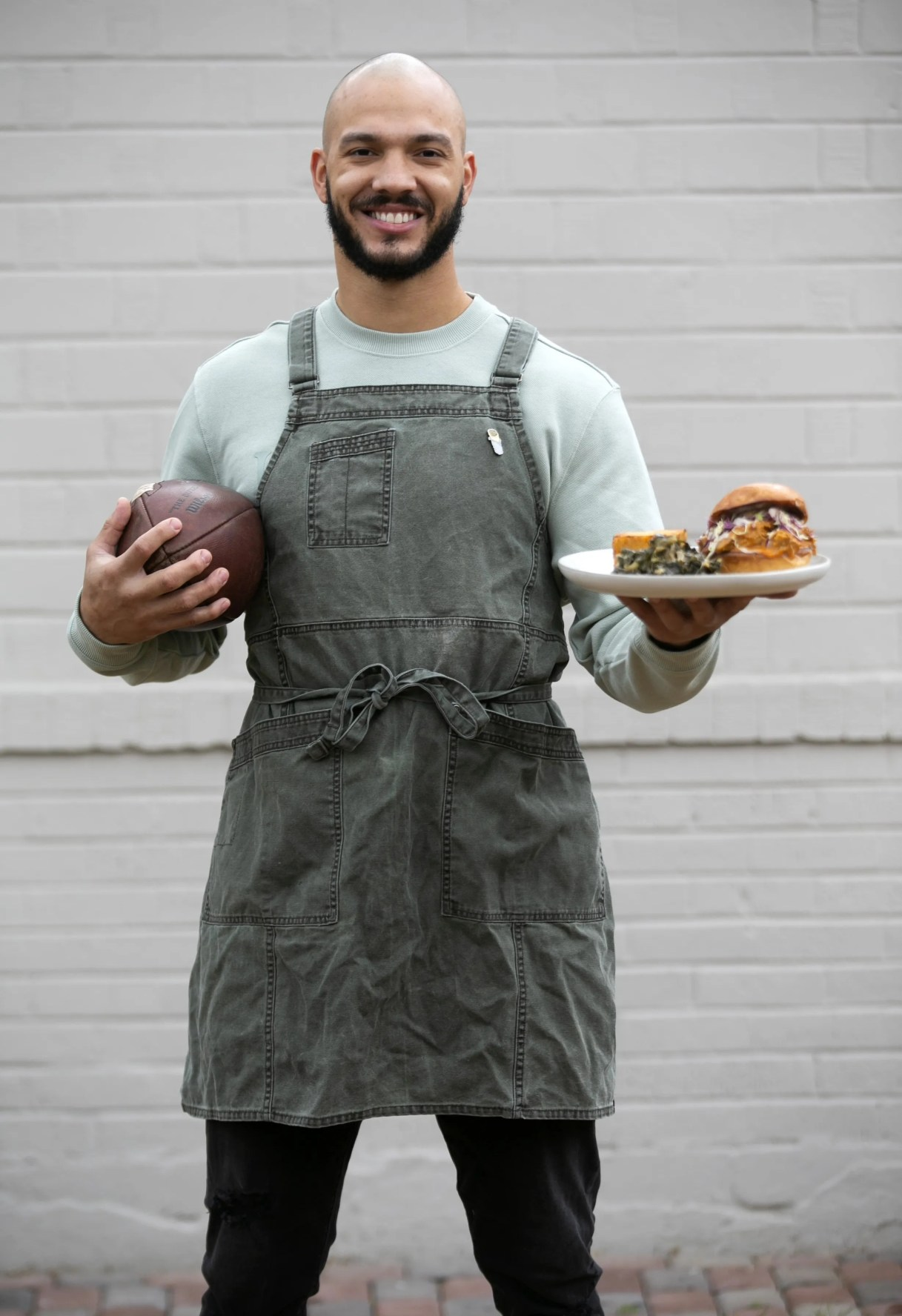 """Phoenix chef and former college football player Lawrence """"L.T."""" Smith holds his signature pulled pork sandwich topped with Carolina Gold sauce. Read his story and learn how to make his game-changing pulled pork sandwich."""