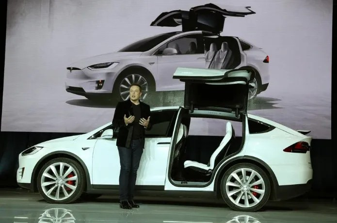 Tesla CEO Elon Musk stands next to a Model X electric sport utility vehicle during a presentation in California in 2015.