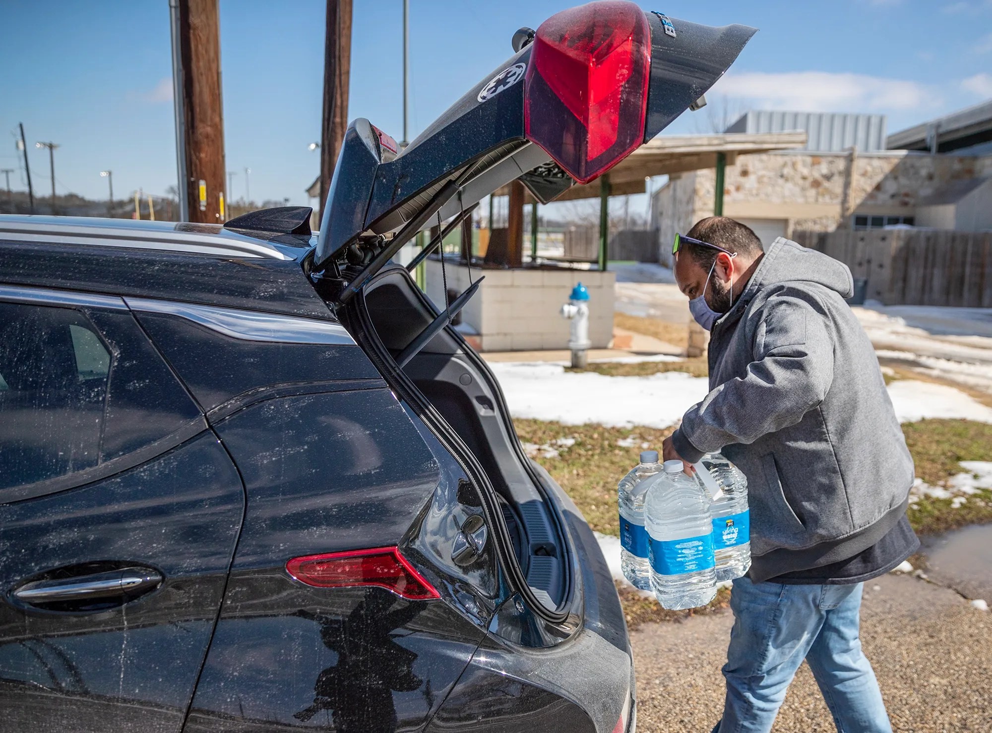Martin Lopez loads his car with water after refilling the bottles at Georgetown Community Center in Texas on Feb.19.