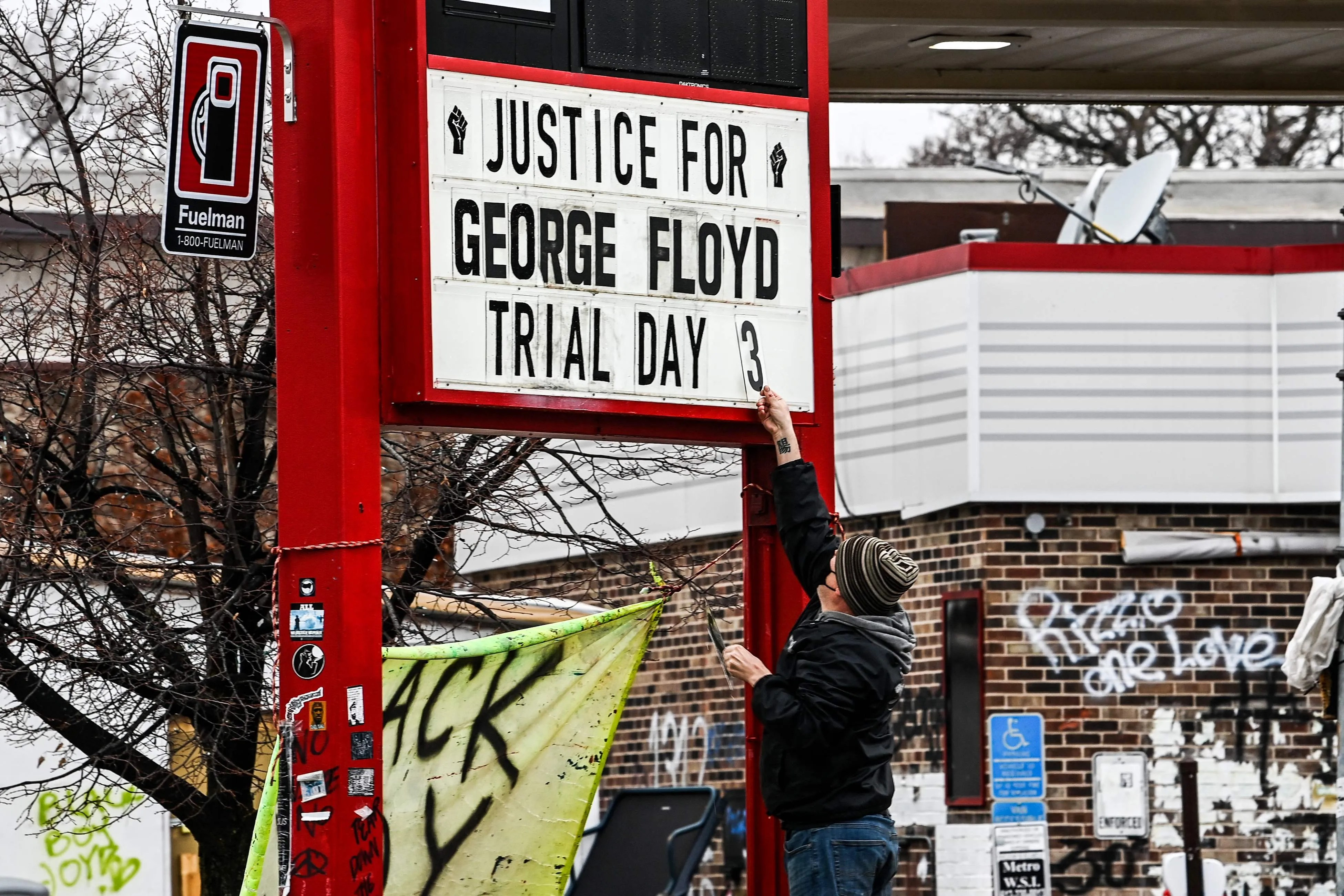 A man changes the number of a sign board at a makeshift memorial of George Floyd before the third day of jury selection begins in the trial of former Minneapolis Police officer Derek Chauvin who is accused of killing Floyd, in Minneapolis, Minnesota on March 10, 2021.