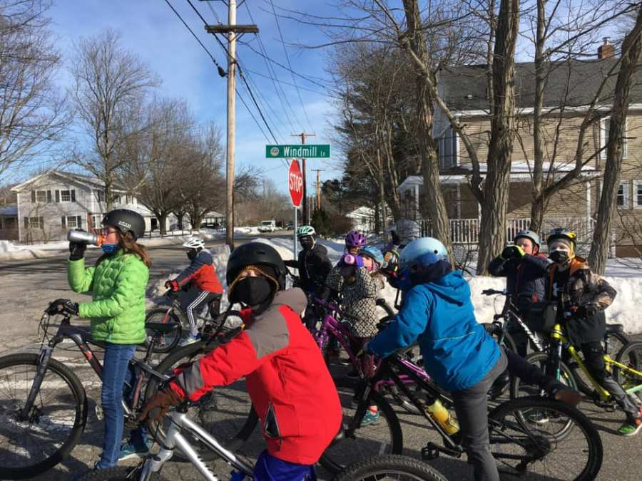 Second and third graders with a fifth grade junior coach, in green, take a water break after riding up the long Windmill Road climb in Hampton.