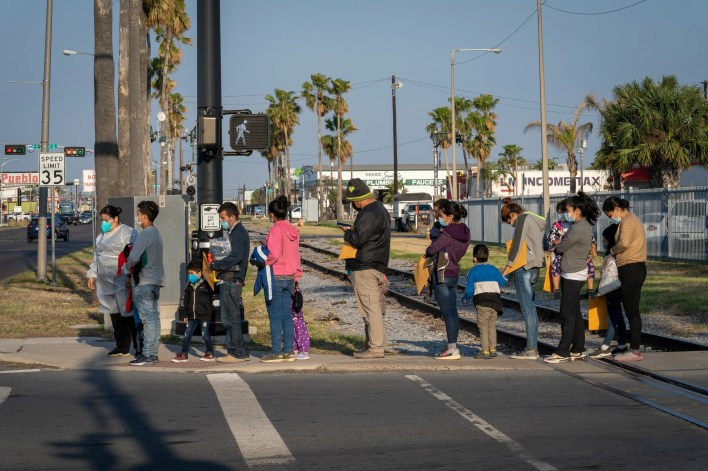 A group of migrants is led from a COVID-19 testing center run by Catholic Charities to the organization's nearby respite center on Monday, March 22, 2021, in McAllen, Texas.