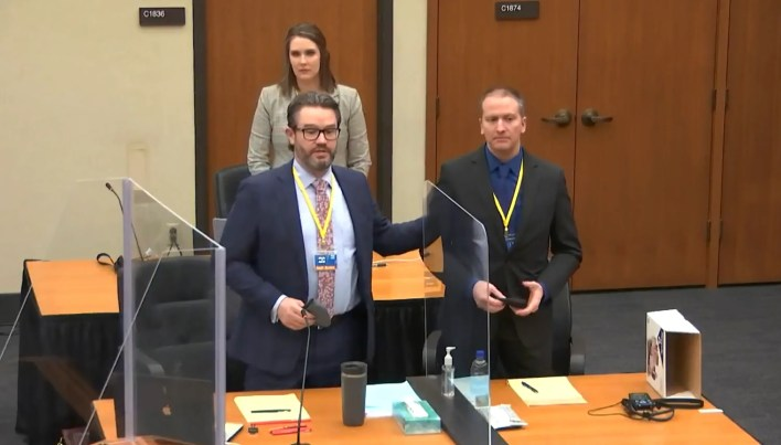 In this screen grab from video, defense attorney Eric Nelson, left, stands with Derek Chauvin, right, and Nelson's assistant Amy Voss, back, to introduce themselves to potential jurors March 23 at the Hennepin County Courthouse in Minneapolis.