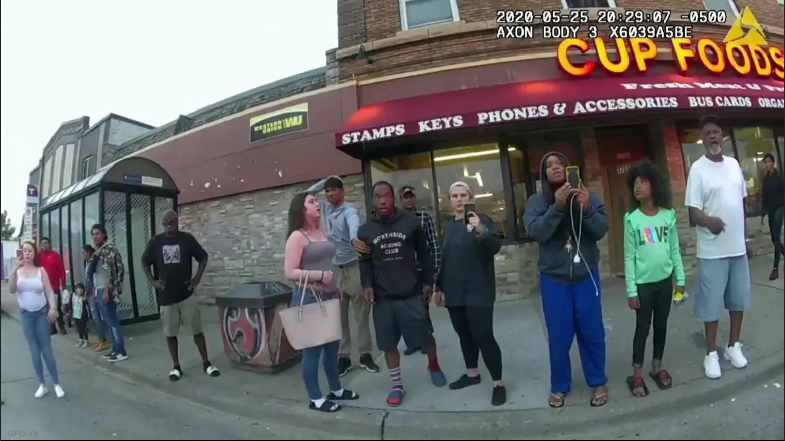 Police body camera shows bystanders watching Minneapolis police officer Derek Chauvin subdue George Floyd in Minneapolis, including Alyssa Funari, left, filming; Charles McMillian, center left in light colored shorts; Christopher Martin, center in gray; Donald Williams, center in black; Genevieve Hansen, fourth from right, filming; and Darnella Frazier, third from right, filming.