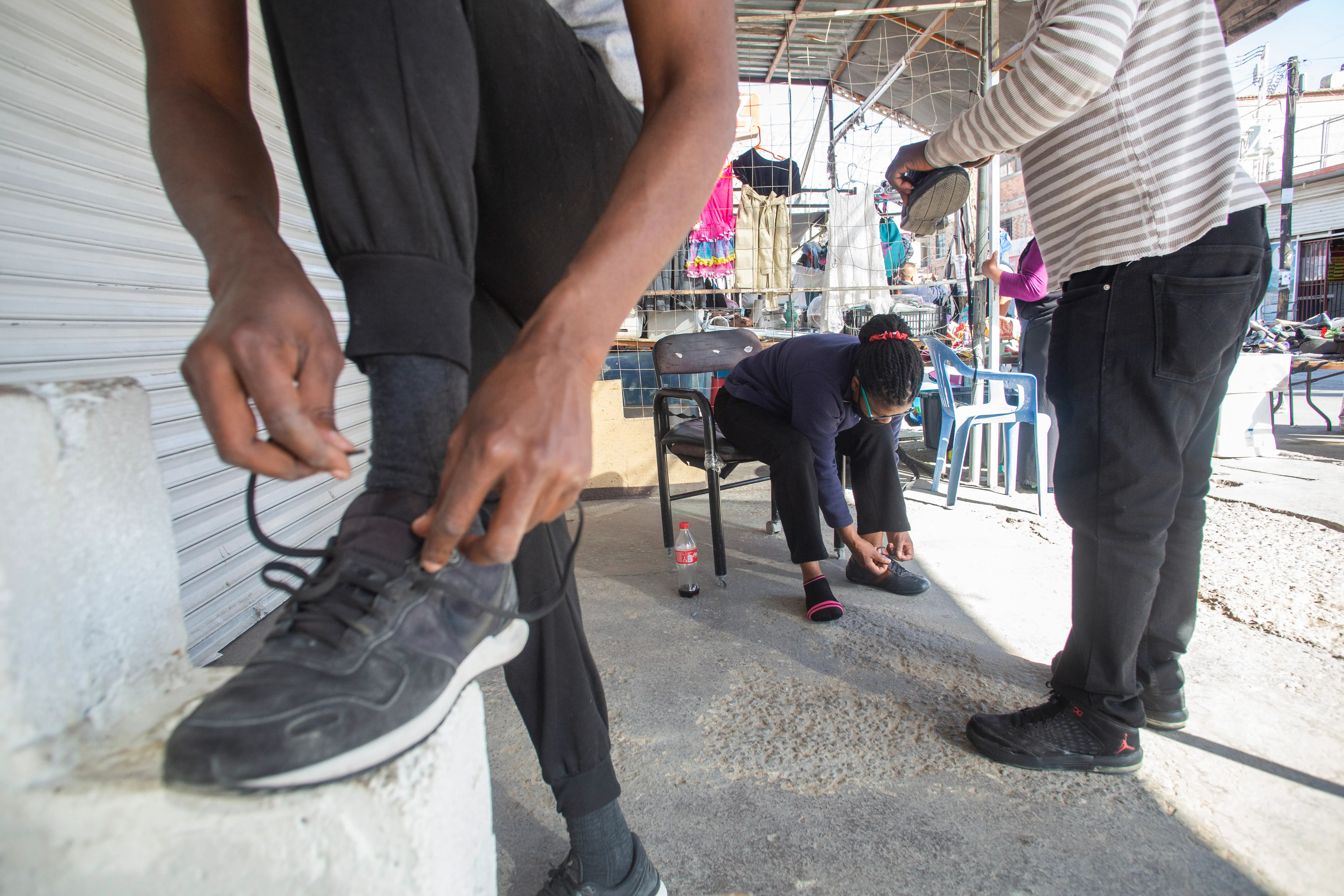 From left, Herve Alverna, Marie Martine and Fanfan Jean lace up their shoes after a street vendor in downtown Cuidad Juarez gives them free shoelaces. The migrants' shoelaces and belts were taken from them by U.S. Border Patrol, a typical security measure, when they entered the U.S. without proper documentation.