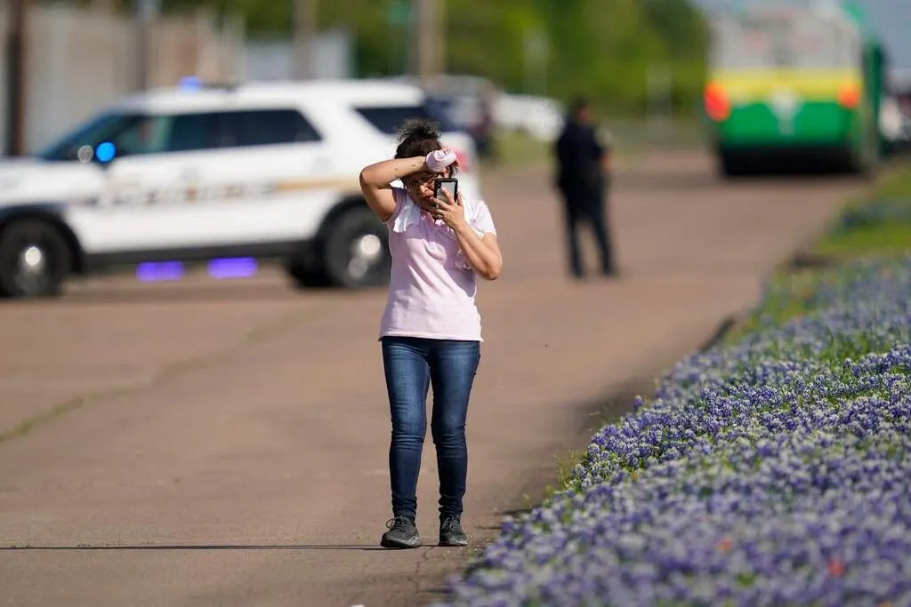 An employee from a local business talks on her phone after police released her from the scene of a mass shooting at an industrial park in Bryan, Texas on April 8, 2021.