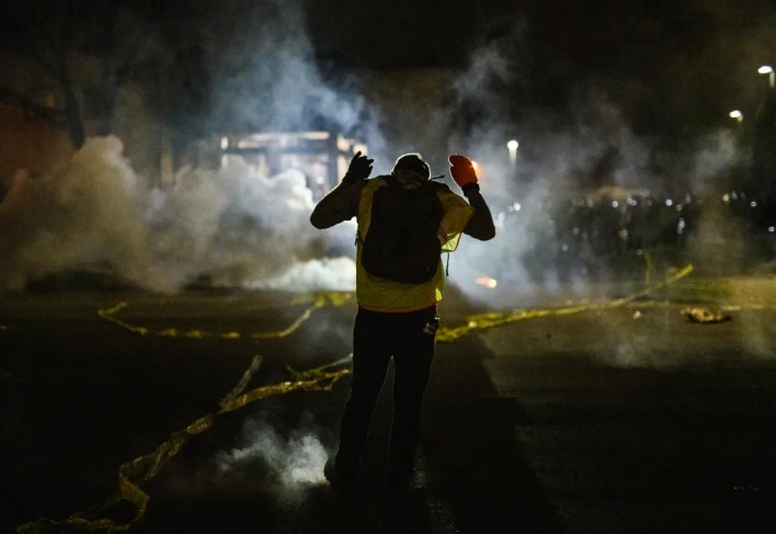 Tear gas fills the air as people confront police outside the Brooklyn Center police headquarters on April 11 in Minnesota. Protesters took to the streets after Daunte Wright was shot and killed during a traffic stop by Brooklyn Center police.