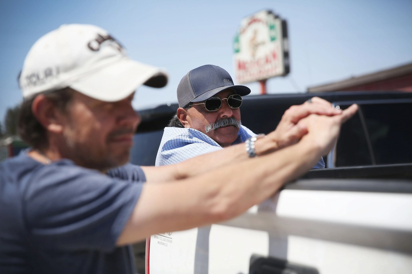 Richard Orona, right, and Bert Montee, left, talk about what they have heard about the migrant children shelter Friday, April 9, 2021, outside of Alfredo's Mexican Restaurant in Pecos. Orona and Montee work for a pipeline construction company out of Giddings.