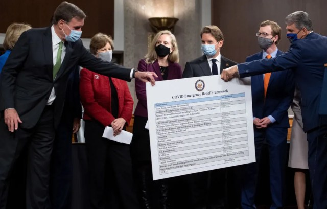U.S. Sen. Joe Manchin, right, hands a poster describing a proposal for a Covid relief bill to U.S. Sen. Mark Warner, alongside a bipartisan group of Democrat and Republican members of Congress as they announce the proposal on Capitol Hill on Dec. 1, 2020.