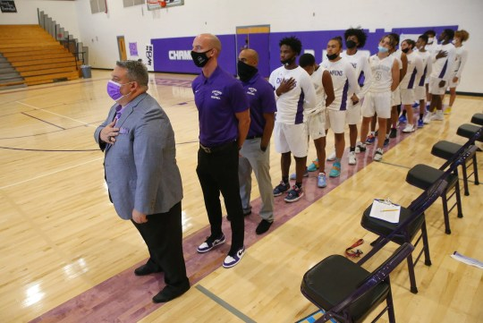 Cesar Chavez head coach Joe Esposito stands for the national anthem with his team before playing against North in Phoenix April 19, 2021.