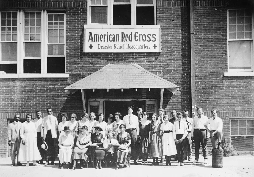 Staff members stand in front of the American Red Cross Disaster Relief Headquarters in Tulsa after the race massacre of June 1921.