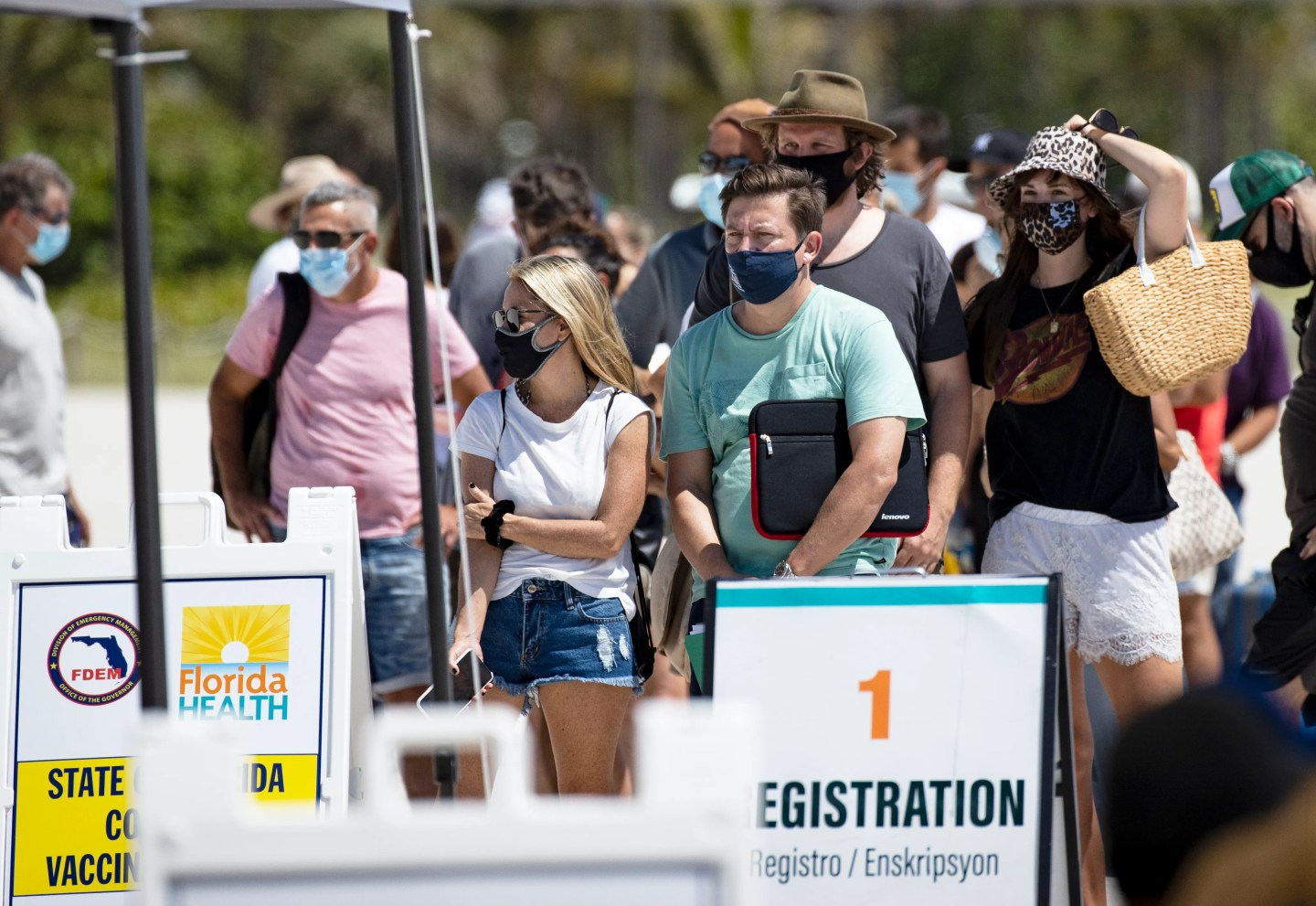 People wait in line Sunday to receive a COVID-19 vaccine at a one-time pop-up vaccination site in Miami Beach.