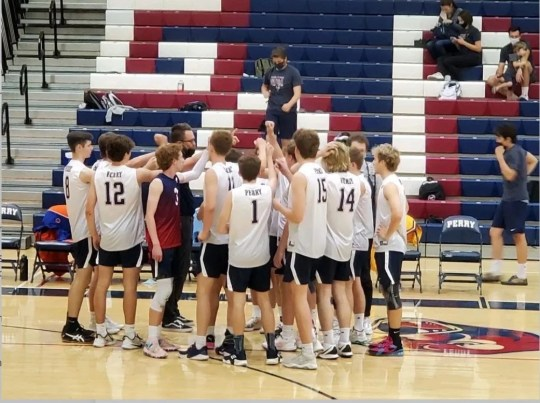 Perry High School's boys volleyball team gathers with coach Ryan Tolman during a recent match.