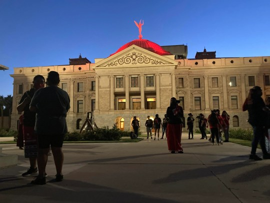 The Arizona state Capitol is lit up red at dusk for Missing and Murdered Indigenous People Awareness Day on May 5, 2021.