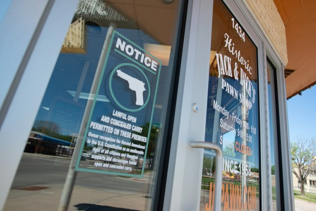 A notice to customers entering Jack and Dick's Pawn Shop in Junction City, Kansas, lets the public know they can carry firearms inside.