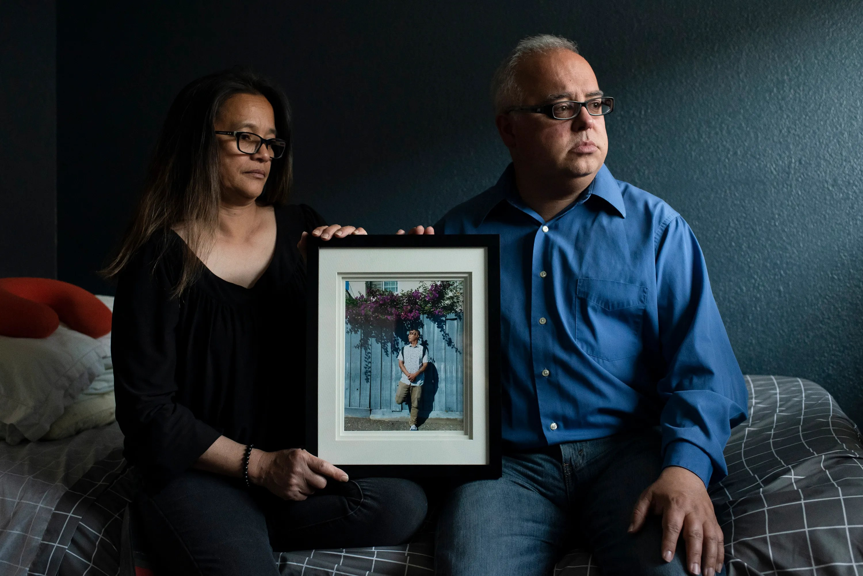Angelo's parents Cassandra Quinto-Collins, left, and Robert Collins, right, hold a photo of Angelo in Angelo's bedroom on May 9, 2021 in Antioch, Calif. Angelo Quinto, a 30-year-old Filipino Navy veteran, was killed by an Antioch, Calif. police officer in Dec. 2020 while experiencing a mental health crisis. Quinto's sister, Bella Collins, had called police to their family home after Angelo began acting unusually. The officer pinned Angelo's neck with his knee; a video taken by a family member shows Angelo unconscious under the weight of the officer's knee. He died three days later, after being taken to the hospital.