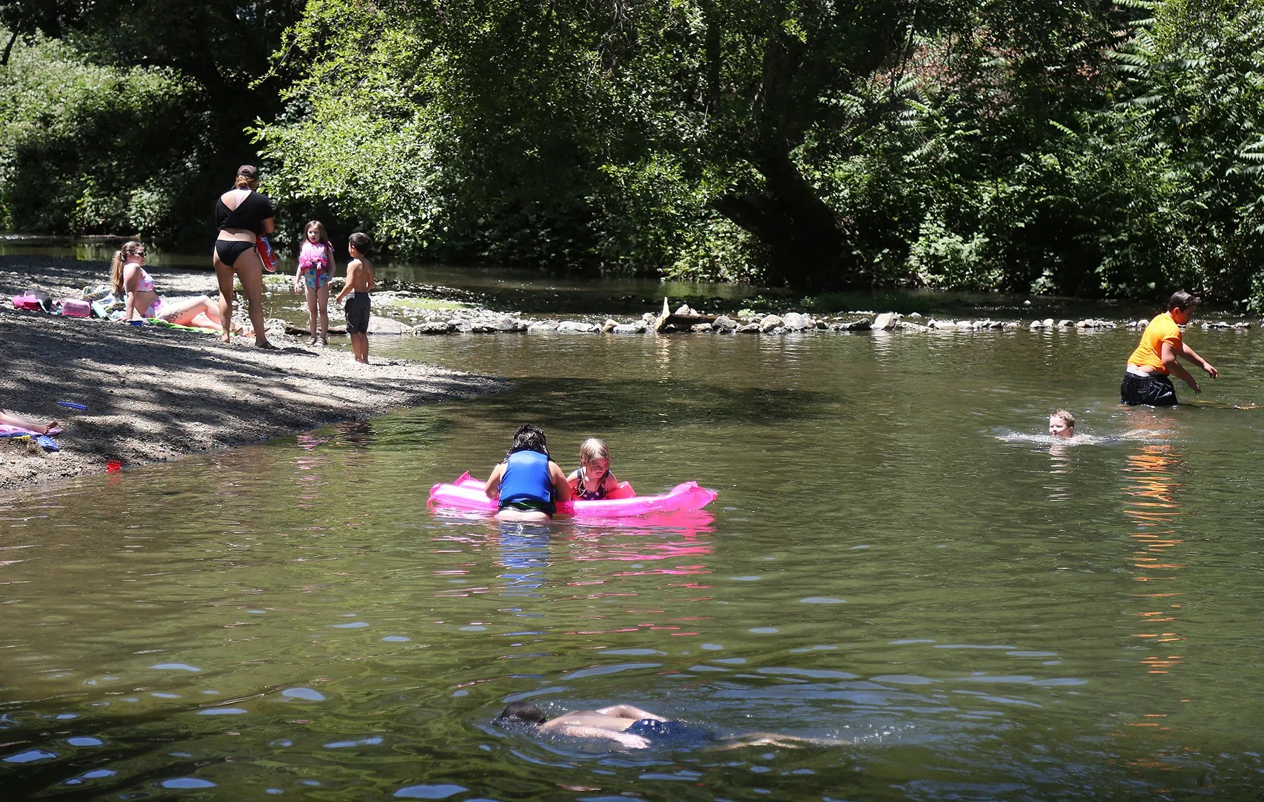 Families beat the heat in the calm and shallow waters of Squirrel Creek Tuesday afternoon, June 15, 2021, in  Western Gateway Park in Penn Valley, Calf. High temperatures are expected to hit the 108 degree mark Thursday and Friday.