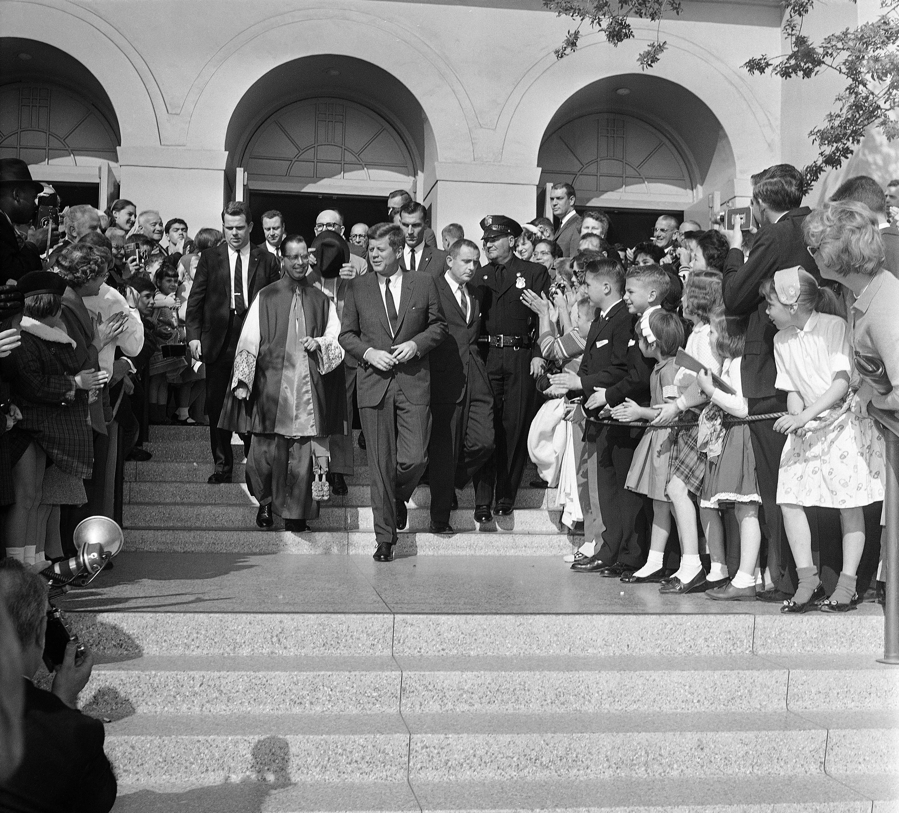 U.S. President John Kennedy leaves the Church of the Good Shepherd in Beverly Hills, California, on Nov. 19, 1961 to the applause of parishioners gathered in front to watch him after he attended Mass. Escorting him to his limousine is the very Rev. Msgr. Daniel F. Sullivan, pastor of the church. (AP Photo/HF)