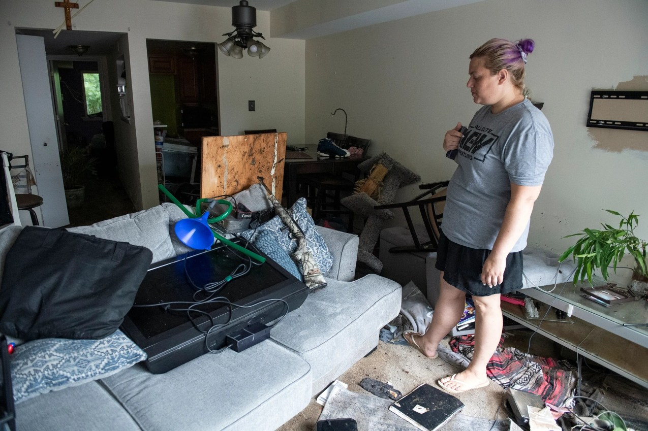 Tiffany Waldron surveys damage to the home of her sister Connie Leon Tuesday, July 13, 2021 at the Lafayette Gardens condominium complex in Bensalem, Pa.