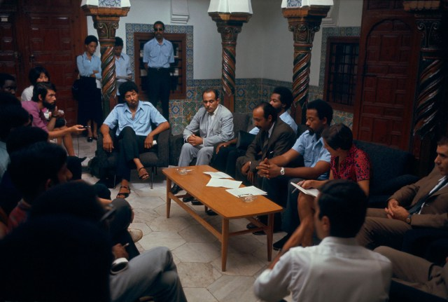 The spokesman of the Black Panther Party, Eldridge Cleaver, (third from right) sits surrounded by party members and others in Algiers, Algeria, in 1970.