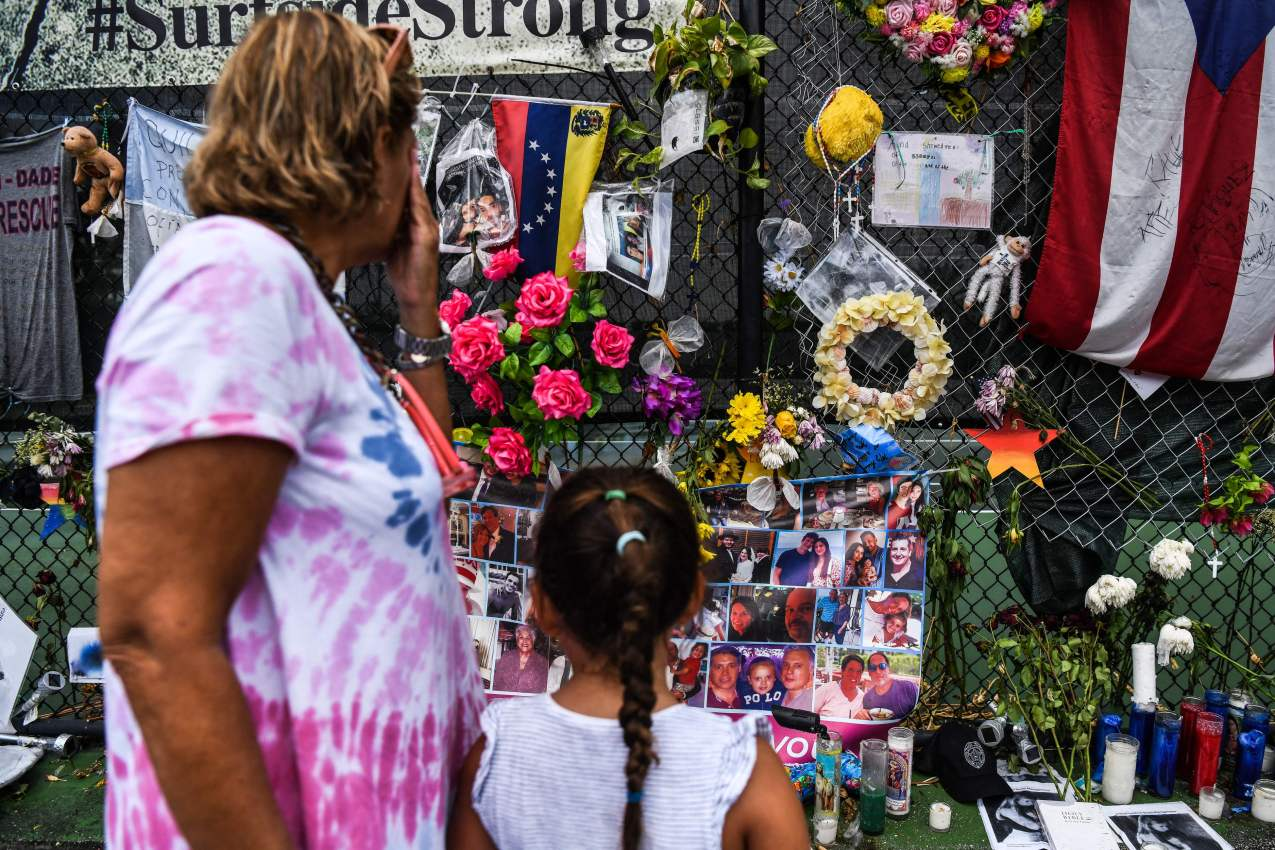 A woman cries as she visits a makeshift memorial where the partially collapsed Champlain Towers South building stood in Surfside, Florida.