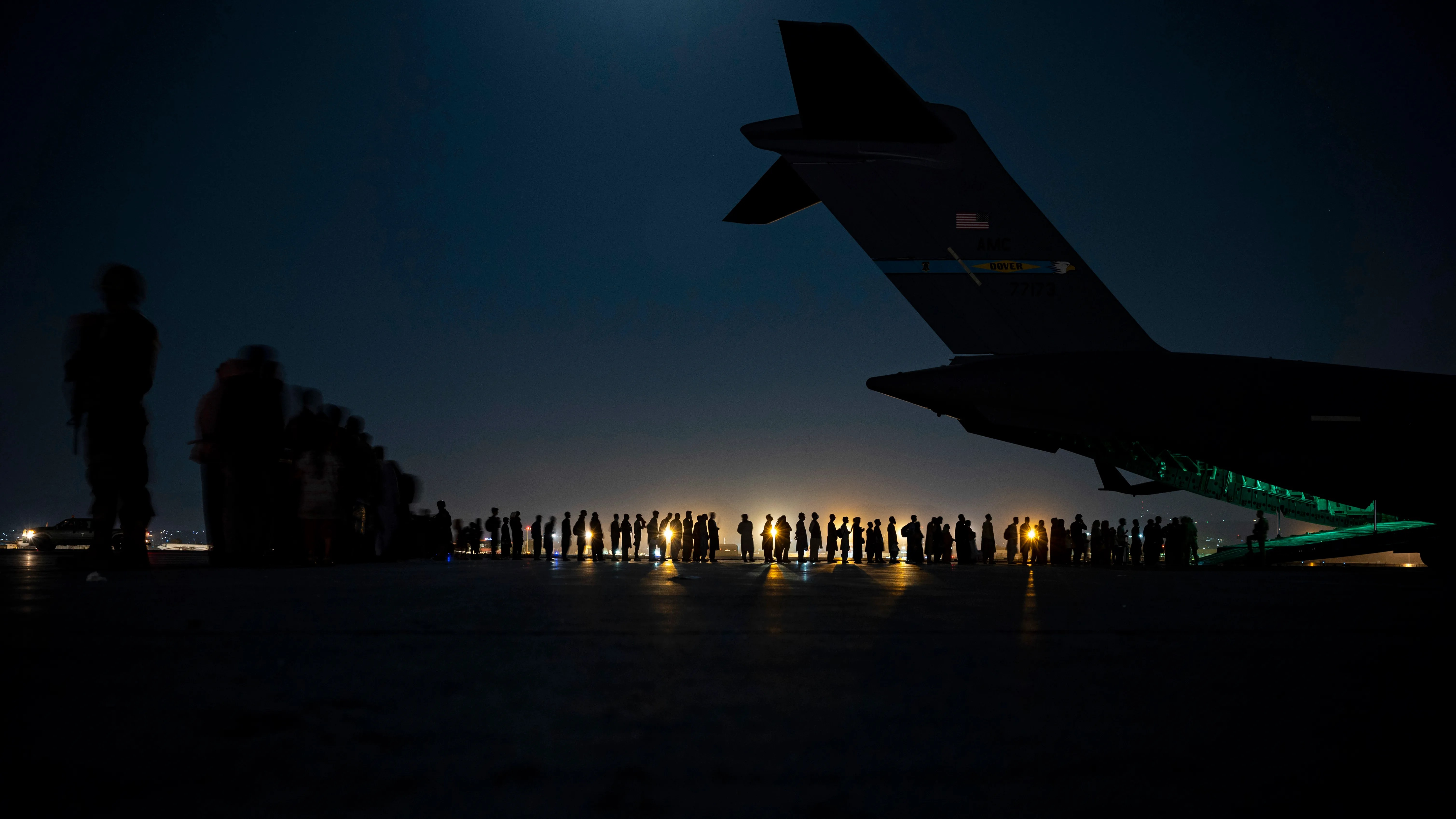 In this image provided by the U.S. Air Force and distributed by AP, U.S. Air Force aircrew, assigned to the 816th Expeditionary Airlift Squadron, prepare to load qualified evacuees aboard a U.S. Air Force C-17 Globemaster III aircraft in support of the Afghanistan evacuation at Hamid Karzai International Airport in Kabul, Afghanistan, on Aug. 21, 2021.