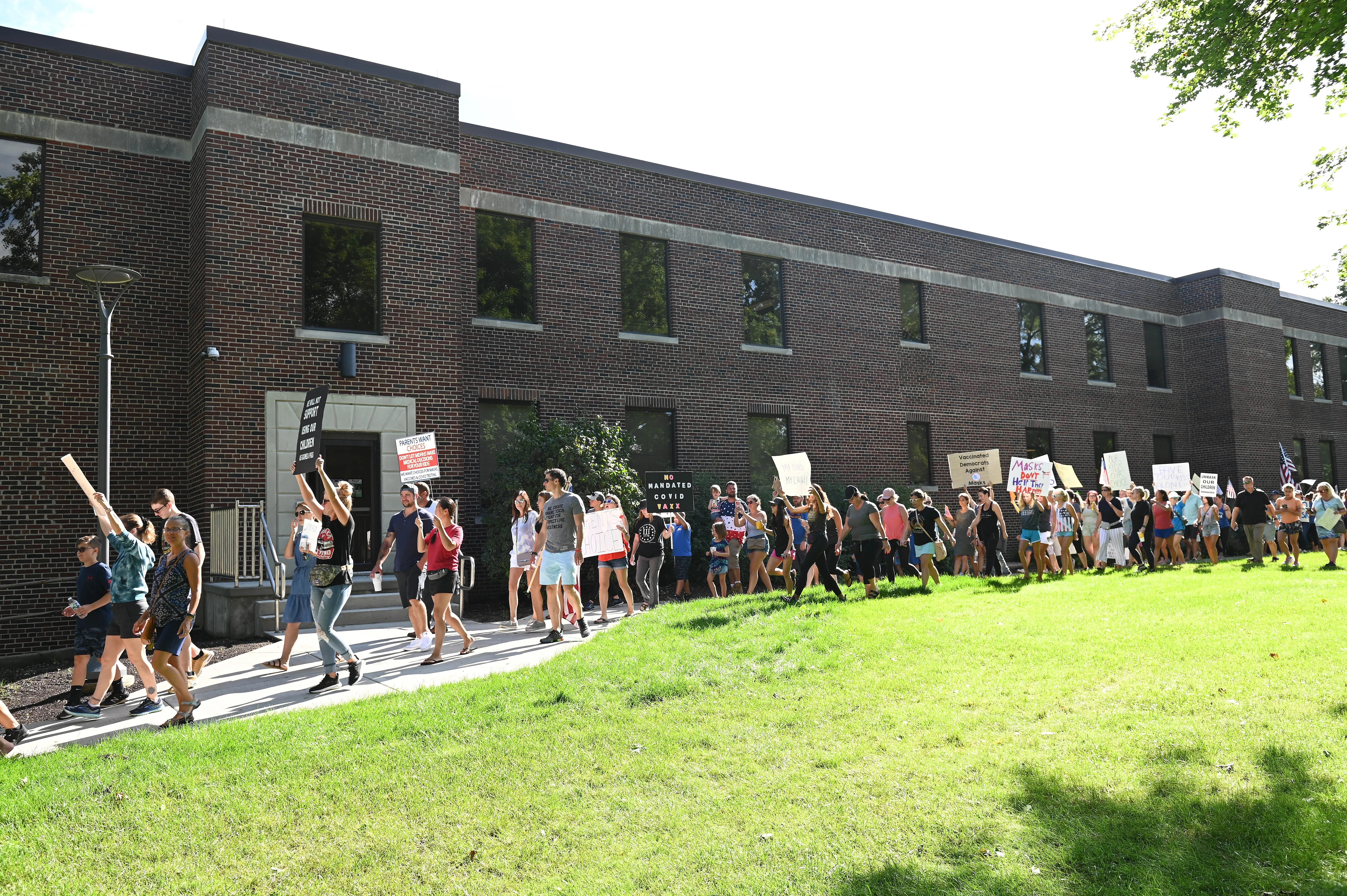 Protesters march around the Oakland County Health Division at a protest in Pontiac on Wednesday, Aug. 25, 2021.