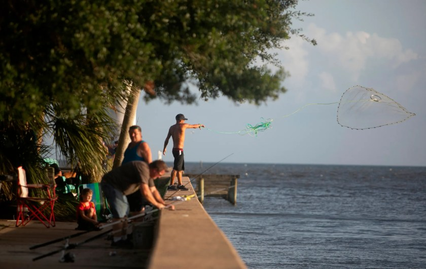 People fish in the old Broadwater Marina in Biloxi, Miss., Saturday, Aug. 28, 2021, ahead of Hurricane Ida, which is expected to make landfall on Sunday.