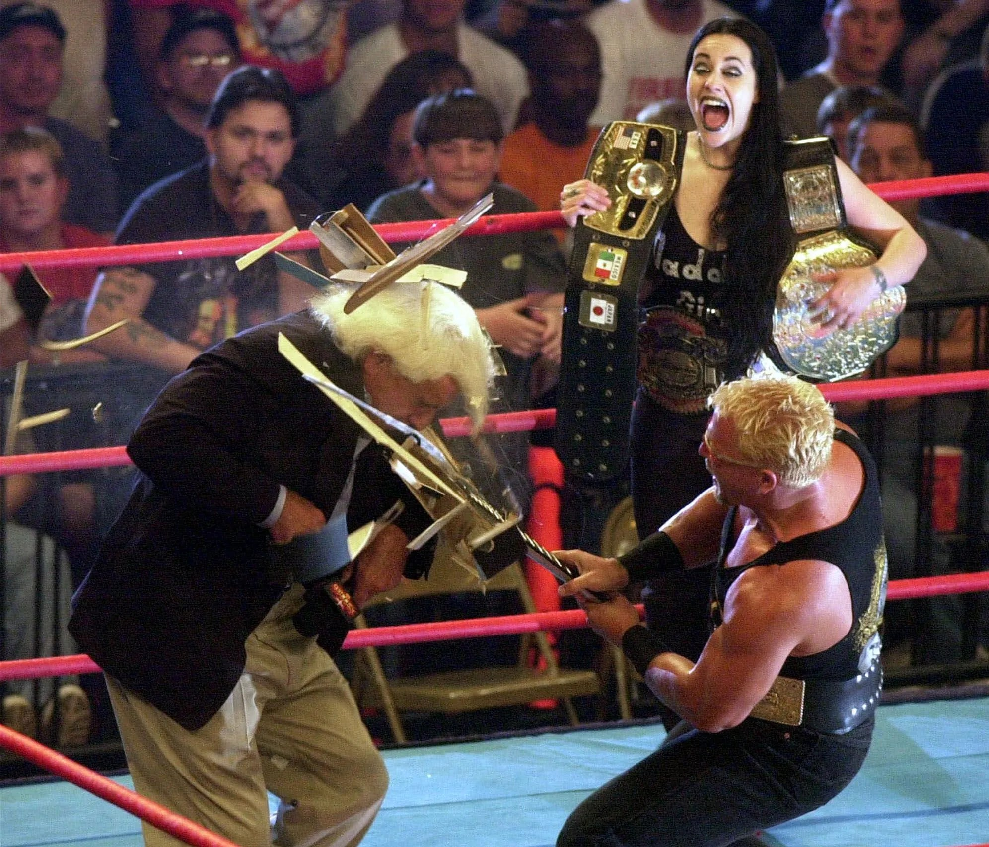 Daffney Unger looks on as Jeff Jarrett, right, smashes a guitar over the head of Ric Flair during WCW's Monday Nitro on May 15, 2000.