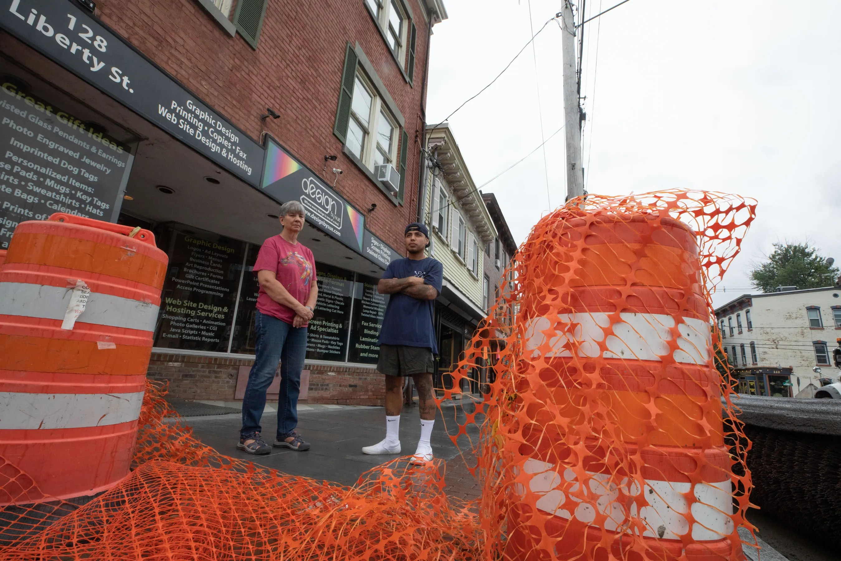 Designs by Sue owner Sue Young, left, and Casa De Fxdes Barberparlor owner Efrain Gordo Acosta, right, stand in front of their businesses in Newburgh, where streetscape construction has been ongoing.