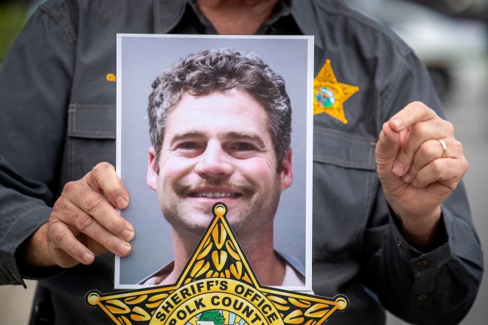 Polk Sheriff Grady Judd holds up a photo of 39-year-old Shaun Runyon, who was captured after a 2-hour manhunt. Runyon was wanted in the deaths of two victims who were attacked at a house in Davenport, Fla., on Saturday, Oct. 2, 2021. ERNST PETERS/ THE LEDGER