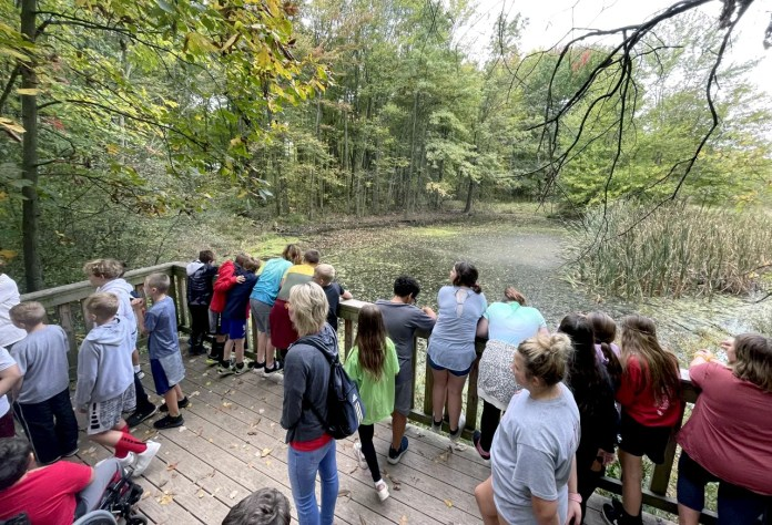The students lean over the railing to get a closer look at Koehler's Pond, also known as the frog pond, to try and see some resident frogs. While at the pond, volunteer Carol Smith taught the students the difference between a frog and a toad so they could identify them correctly.