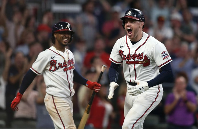 Freddie Freeman celebrates with teammate Ozzie Albies, left, after hitting the go-ahead home run in Game 4 of the NLDS against the Brewers.