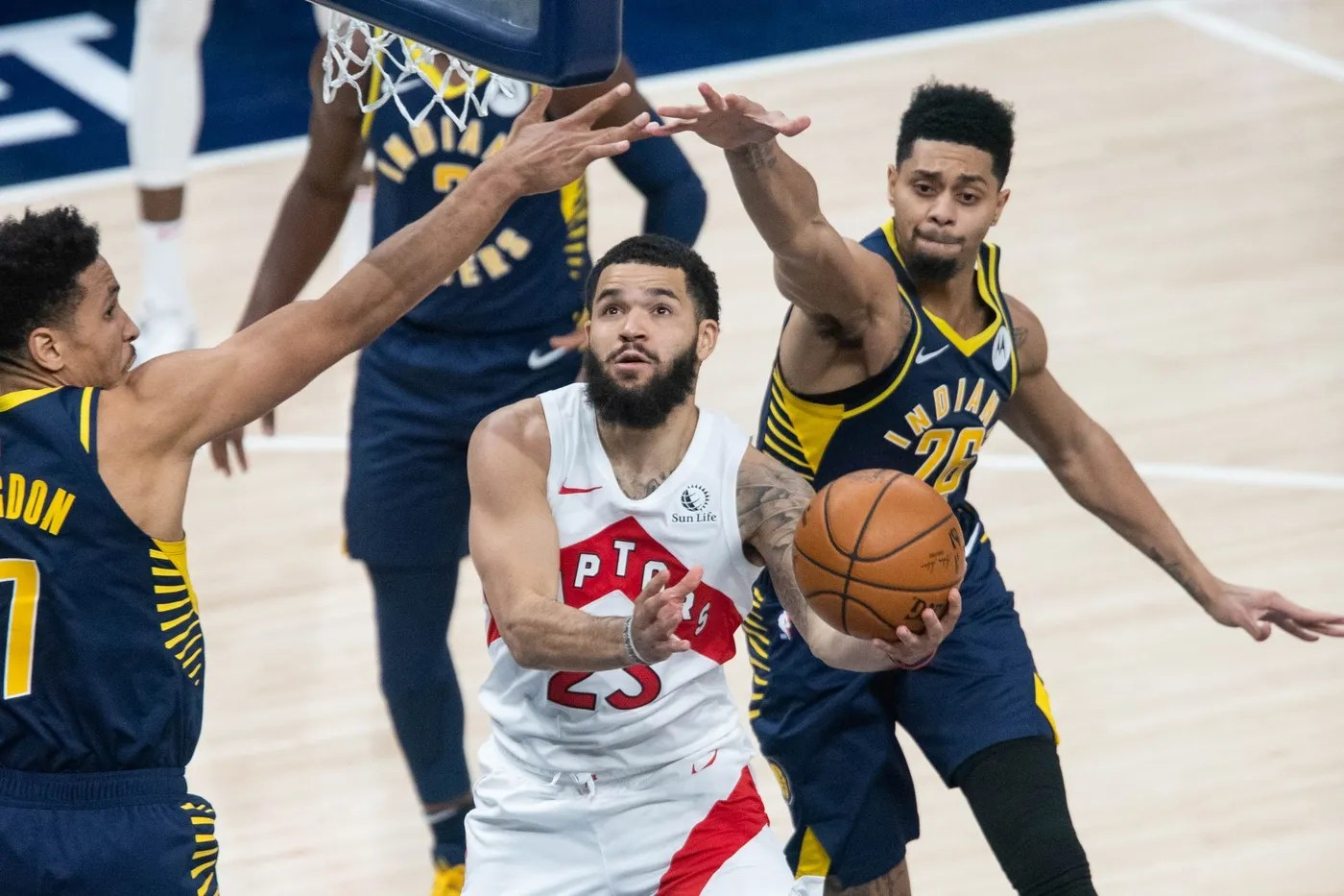 Jan 25, 2021; Indianapolis, Indiana, USA; Toronto Raptors guard Fred VanVleet (23) shoots the ball in between Indiana Pacers guard Malcolm Brogdon (7) and guard Jeremy Lamb (26) in the fourth quarter at Bankers Life Fieldhouse.
